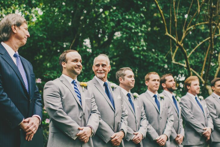 Derick and his groomsmen dressed in gray suits from MH Frank paired with navy ties and a white pocket square. Peach ranunculus boutonnieres were used for a pop of color against the neutral palette.