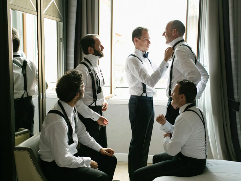 Groomsmen getting ready with groom on wedding morning