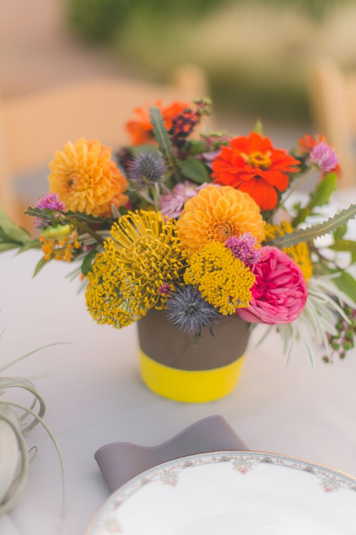 Gray pots filled with zinnias, dahlias, pincushion protea and blue thistle added color and texture to the reception tables.