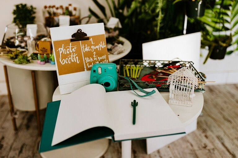 Polaroid camera and guest book on small table