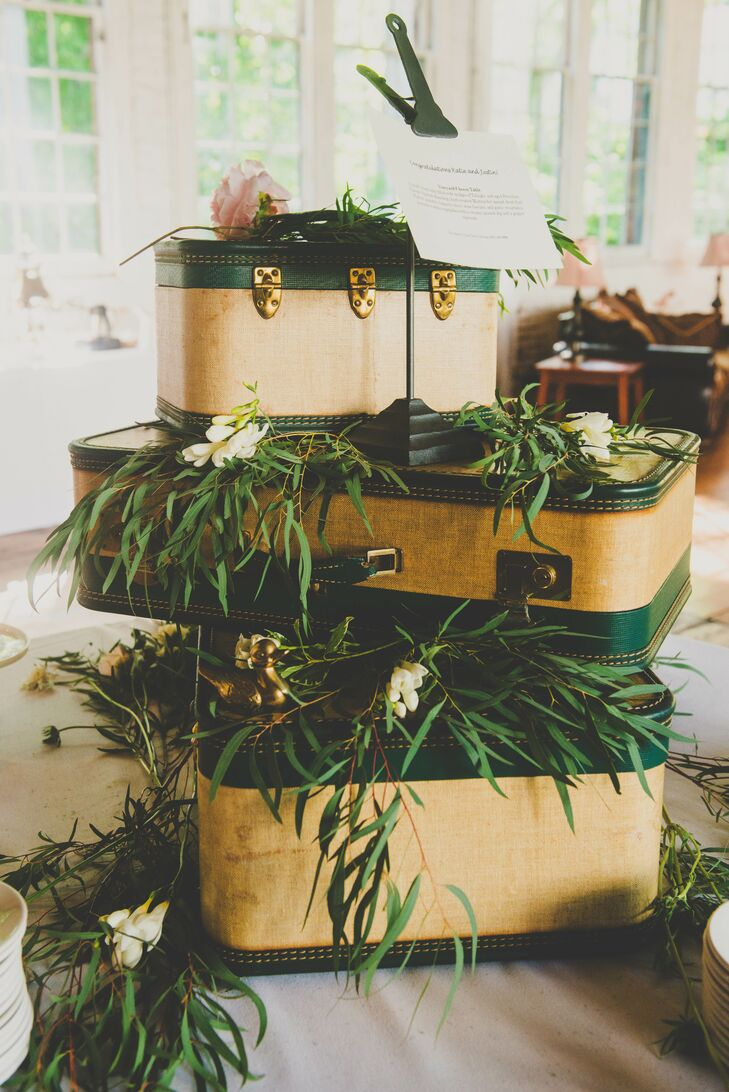 At the reception, a display of yellow and green pieces of luggage were stacked on one another, reflecting the vintage twist within the wedding decor. The luggage was draped with greenery and positioned in the middle of the room.