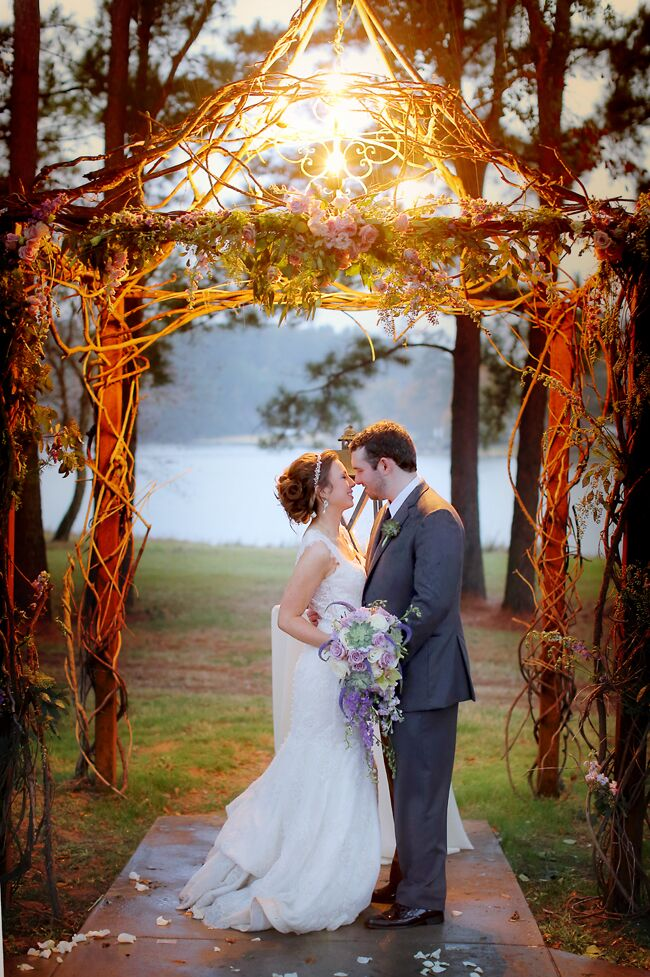 "The wedding arbor stood under a large oak tree and included a chandelier to illuminate the couple as they said ""I do."" ""The arbor we were married under had flowers woven through it, and was just beautiful with the lake behind it,"" the bride says."
