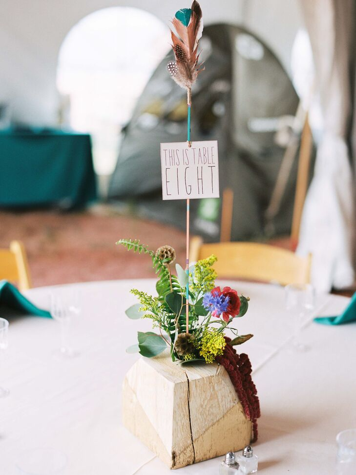 Local beetle kill wood painted gold served as rustic, boho centerpieces. Each one was filled with a colorful mix of local flowers including ranunculus and scabiosa pods. The table number was displayed on a hand-painted arrow decorated with feathers.