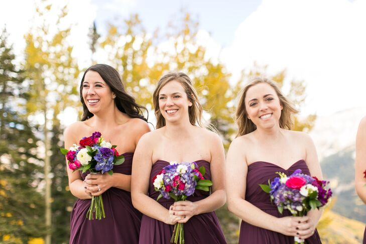 "To complement the day's vibrant fall-inspired palette, bridesmaids wore deep purple strapless gowns and carried deep crimson and lavender-hued bouquets. ""Bouquets were lush, nontraditional fall colors. We loved the look of fluffy flowers and a variety of textures,"" Margaret says."