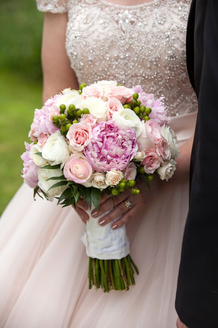 Peonies, roses, ranunculus and hypericum berries filled Haley's round bridal bouquet. The Flower Patch gorgeously arranged the combination of soft shades of pink and green, which fit the romantic palette as well as the natural feel of the outdoor space in Festus, Missouri.