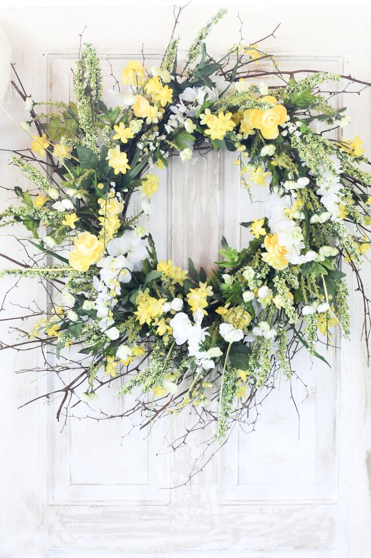 A white and yellow floral wreath was hung on one of the white antique doors that stood behind the couple during the ceremony.