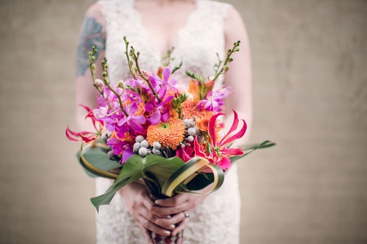 Whitney's beautiful bouquet included pin cushion proteas, orchids, roses, gloriosa lilies, flax leaves, lily grass and monestera leaves. The stems were wrapped in kitenge fabric.