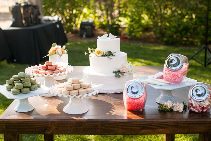 A dessert spread was arranged on top of a wooden table, which included macarons on elegant white stands, brightly colored candy in glass jars and the traditional white wedding cake accented with flowers.