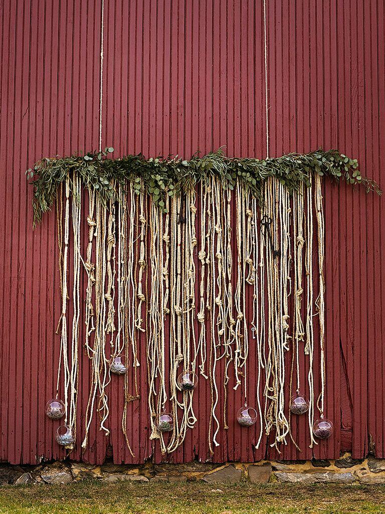 DIY metallic rope and gardland backdrop for an outdoor wedding ceremony