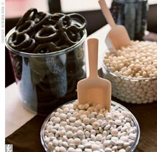 A candy bar filled with white M&Ms, vanilla jelly beans, white rock candy sticks, chocolate covered almonds, and chocolate covered pretzels.