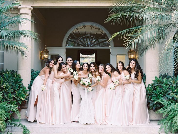 Monique's bridesmaids wore pale pink full-length gowns in a tone similar to the pink peony flower arrangements and bouquets.