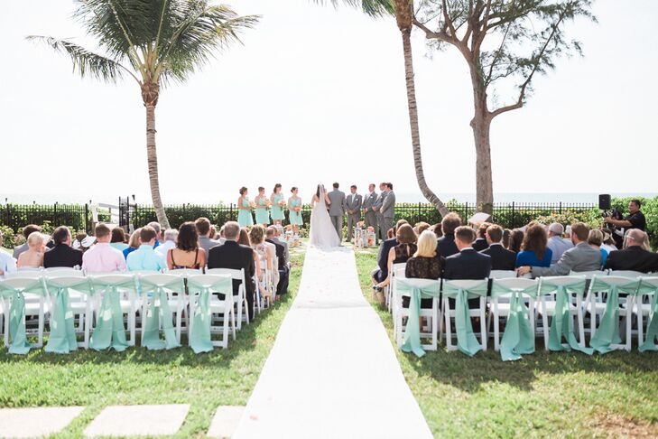 Since mint is Stephanie's favorite color, it was no surprise that it was the first thing guests saw when they entered the afternoon ceremony. The entire back row of white folding chairs was wrapped in mint sashes, which perfectly matched the bridesmaid dresses and groomsmen's ties.