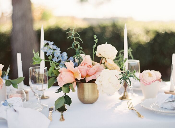 At the reception's ivory linen-topped tables, gold candlesticks and vases sat among peach and blue floral blossoms.