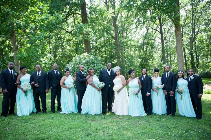 Sicilia and Samuel stood in the middle of their wedding party, lined up outside at Liriodendron Mansion in Baltimore, Maryland. The bridesmaids wore one-shoulder aqua blue-green dresses, while the groomsmen rocked a more classic look with black suits and black bow ties.