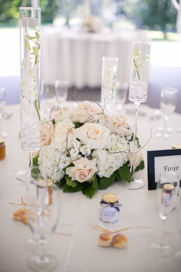 Reception centerpieces alternated between tall and short floral orchid centerpieces, which included blush roses. Tall glass vases were filled with floating flowers.