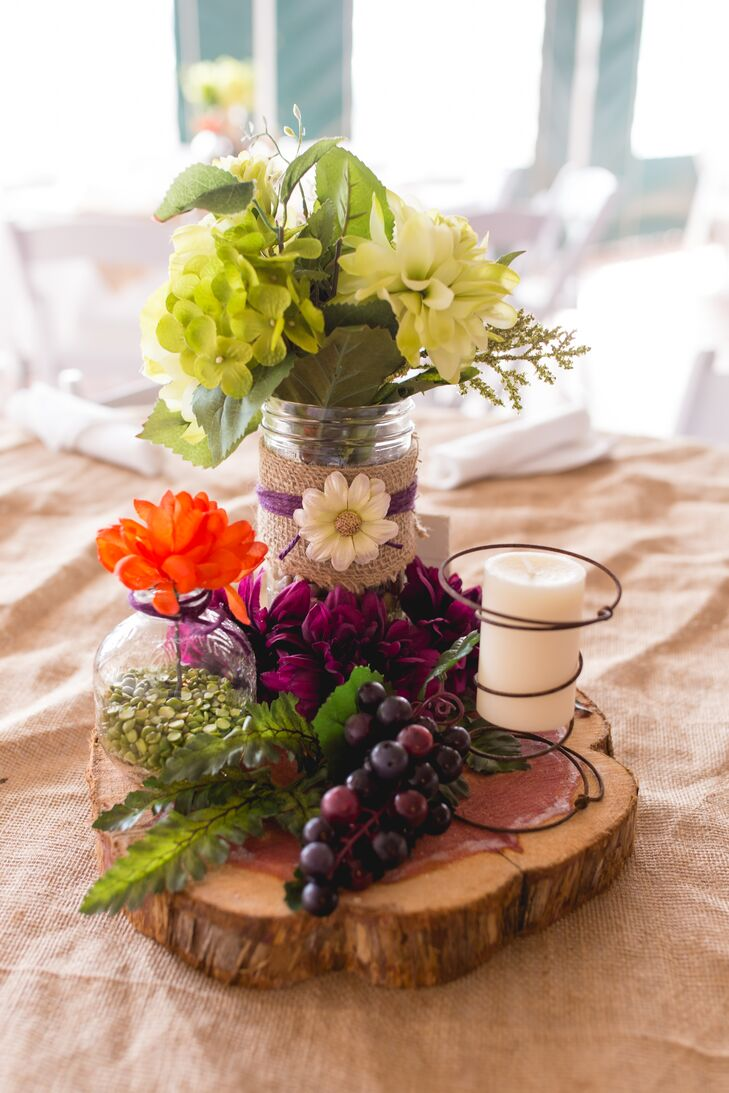 To save on costs and give the day an extra personal touch, Leslie and Roy decided to make a lot of the decor themselves. For the centerpieces, they opted for silk flowers instead of fresh, arranging them in burlap wrapped jars and bud vases. The vases as well as purple grapes, candles and greenery were placed on top of cedar wood rounds to give each table top a rustic, vineyard-inspired look.
