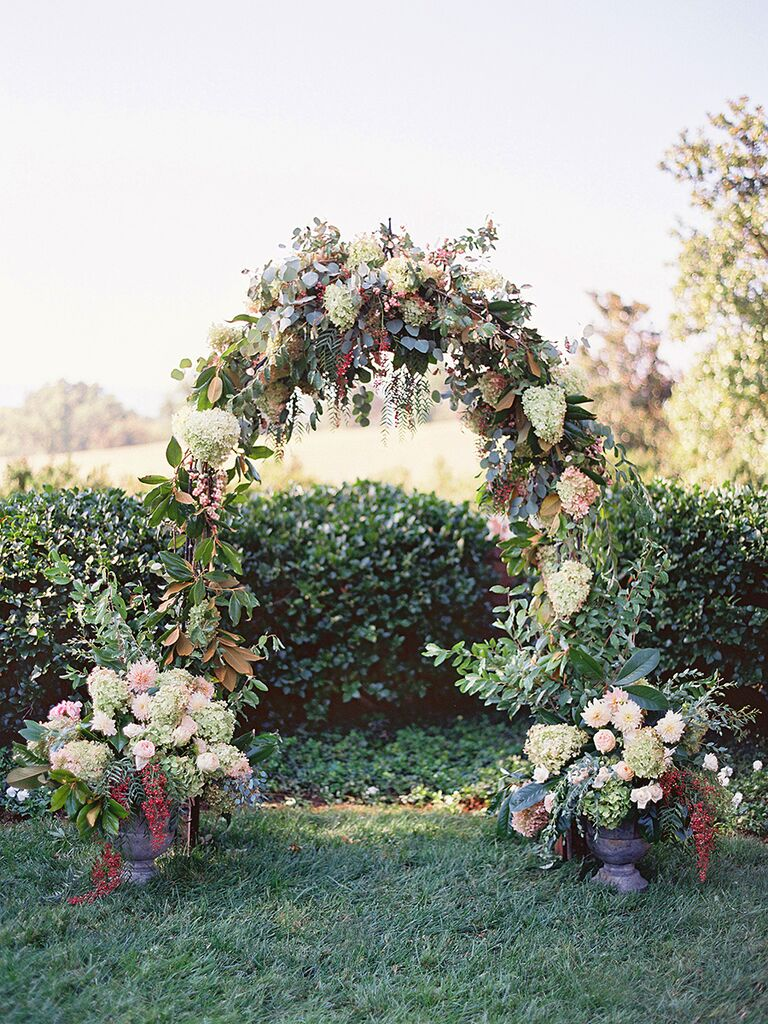 Beautiful hydrangea and rose floral arbor for an outdoor wedding