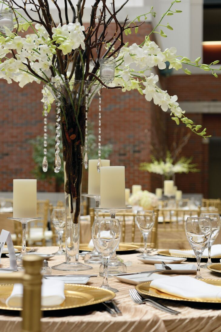 Gold chargers, large vanilla-scented candles and arrangements of orchids and branches in tall trumpet vases topped the pleated champagne-colored table linens.