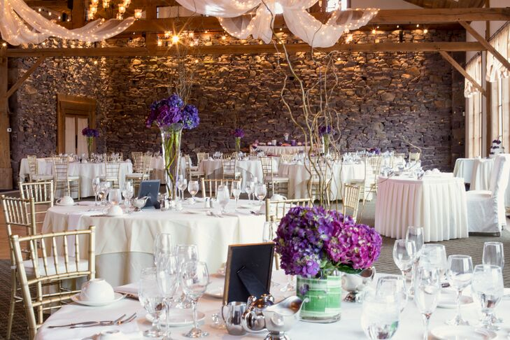 """""""The flowers were unique,"""" Sarah says. The couple's florist, Chantilly Floral Boutique, accented their all-white decor with fun arrangements of purple hydrangeas, pink hydrangeas and branches. Each low or tall centerpiece was paired with a simpler gold and purple table number with a dotted design."""