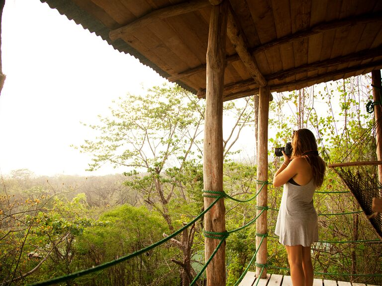 woman standing on a balcony with a camera overlooking beautiful costa rica rainforest and scenery