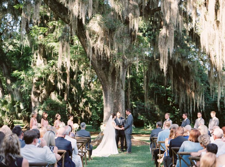 """""""When we discovered Tallahassee's Southwood House and Cottages, we knew it was a perfect fit,"""" Laurie says. They loved the giant oaks draped in Spanish moss, so it served as the backdrop for their sweet, outdoor ceremony. Guests watched the service from wooden chairs as the soon-to-be weds shared personalized vows and live music played in the background. """"My cousin, Katie Fair, played and sang 'By Our Love' by Christy Nockels,"""" Laurie says. """"The words of this song are powerful and speak so closely to the story we want our marriage to tell."""""""