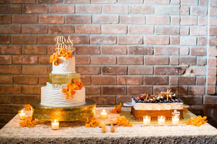 """The wedding cake table was the reception's focal point. Each tier had a different design, with a geometric metallic gold center tier, that included textured details and orange orchids for a colorful pop. A gold """"Mr. & Mrs."""" topper completed the chic style."""