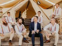 Groom in navy suit with groomsmen in casual boho slacks and rust-colored suspenders
