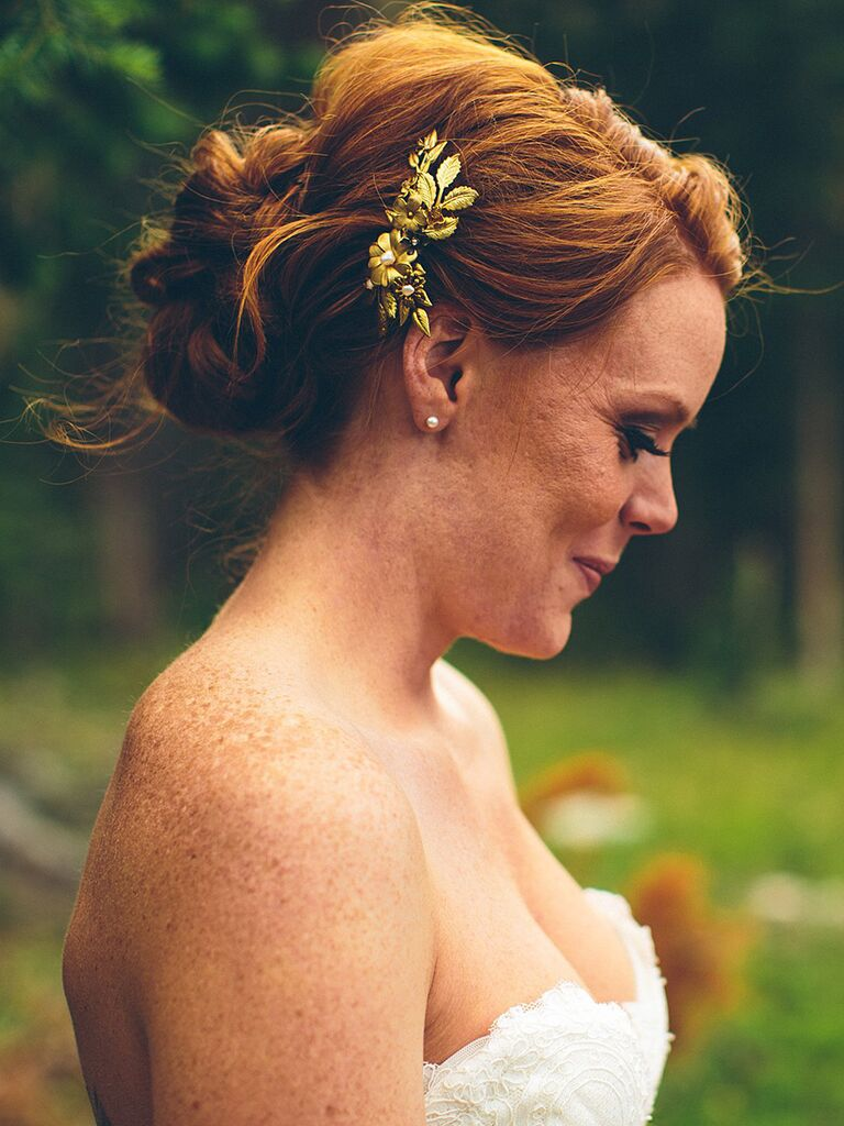 Messy bun wedding updo with a hairpiece