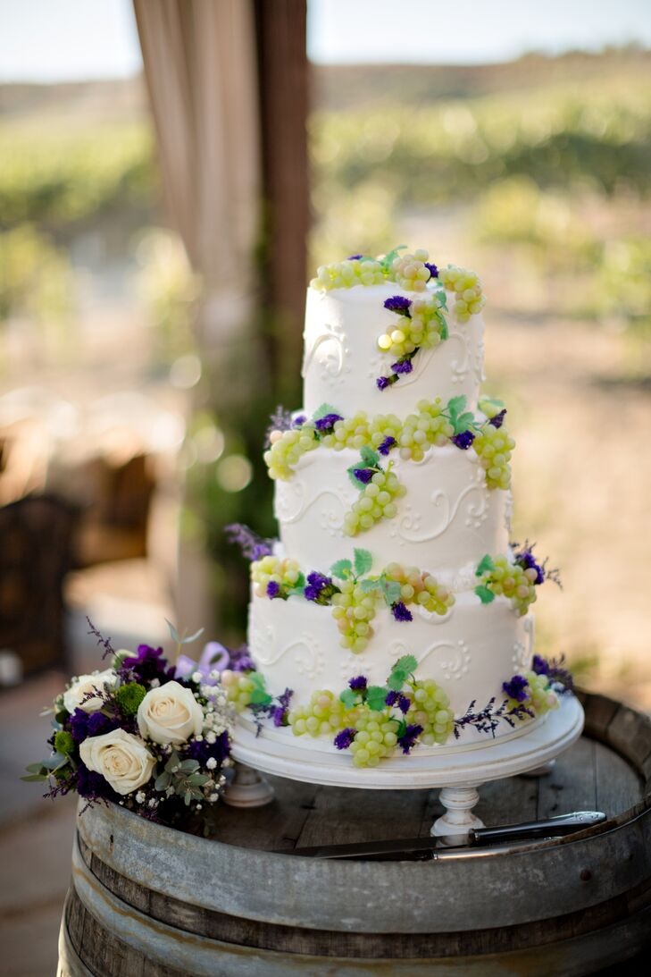 The three-tiered ivory wedding cake was decorated on the top and sides with green grapes and small purple flowers. The cake was positioned on a simple white cake stand.