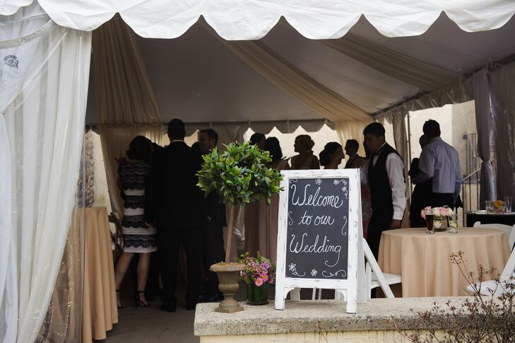 Keeping things simple, the couple marked their tented reception entrance with a low white sign. A mini tree and vase filled with pink wildflowers alluded to the garden-style decor inside.