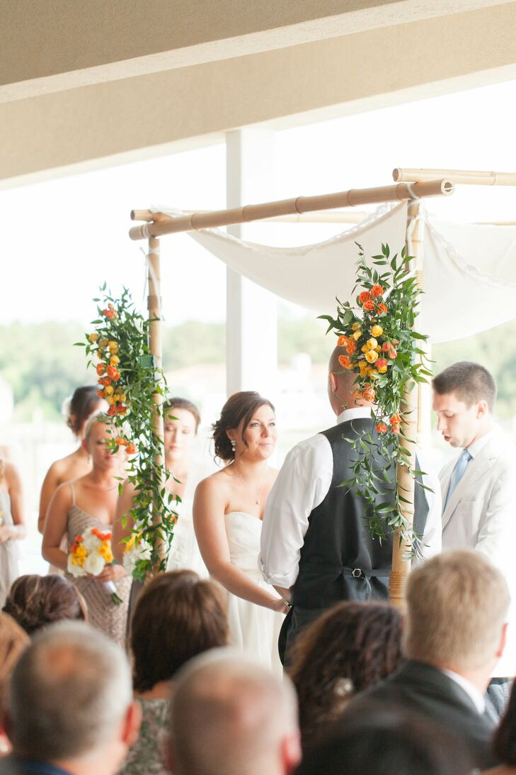 The chuppah at the interfaith ceremony was decorated with flower arrangements of orange and yellow roses.