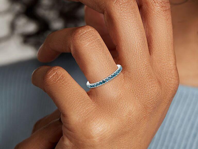 Woman wearing blue topaz pavé ring