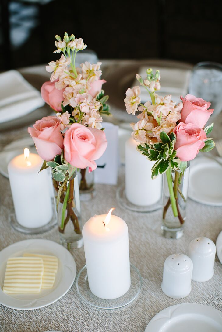 The details for each table setting fit the summer beach wedding theme. Candles set a romantic mood. The all-white plates put the focus on the floral accents.