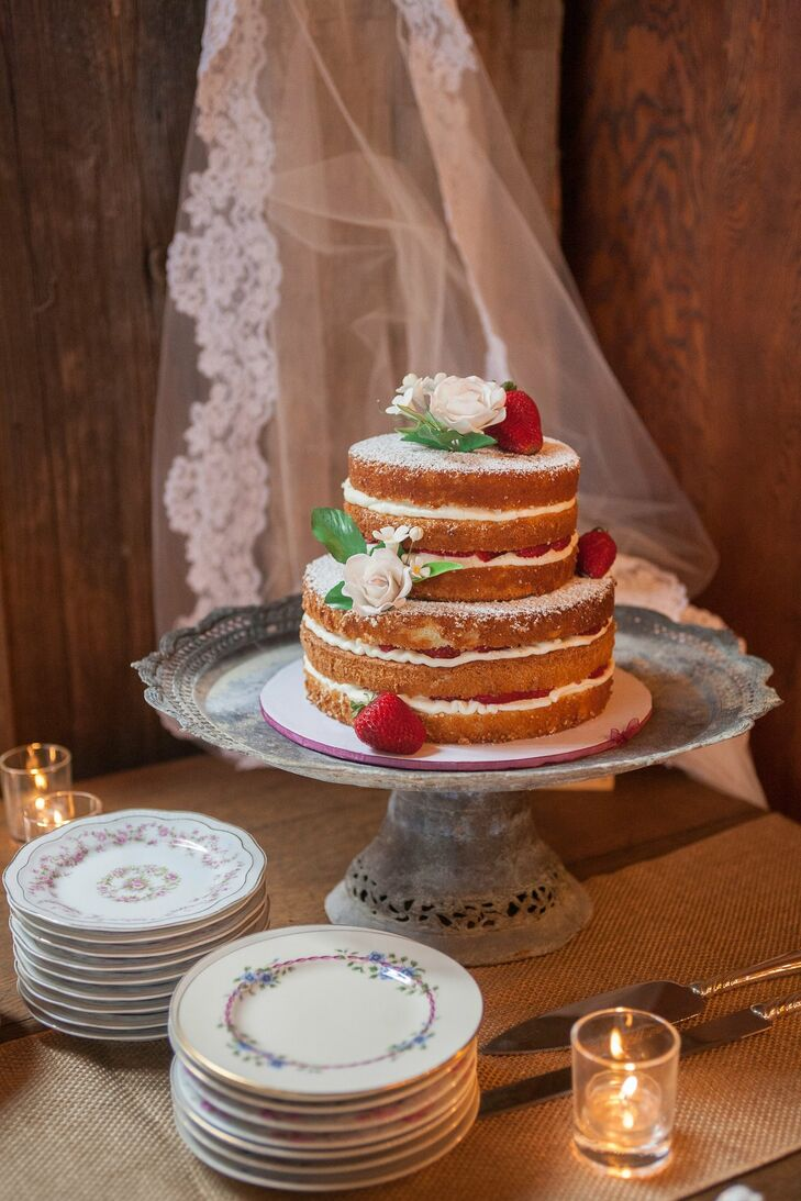 The naked cake had fresh strawberries between the layers and was topped with more berries and sugar roses.