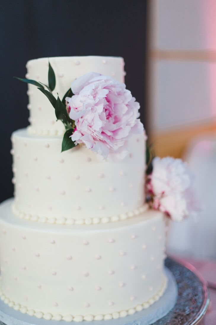 Swiss dots on this white buttercream cake felt timeless, just like Melissa and Matt's wedding. A pair of blush peonies and an elegant silver cake stand dressed up the style.