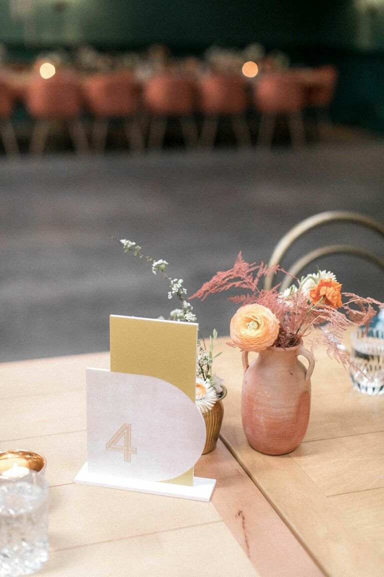 Acrylic table number and small clay vase with ranunculus blooms