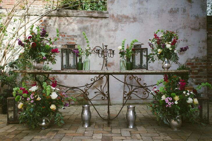 Race & Religious (the venue) has all this cool furniture you can use however you like. Our altar was a table made out of an old door help up by a wrought-iron base, Gretchen says. Lush floral arrangements, pewter accents and antique lanterns lent an air of old-world charm to the decor.