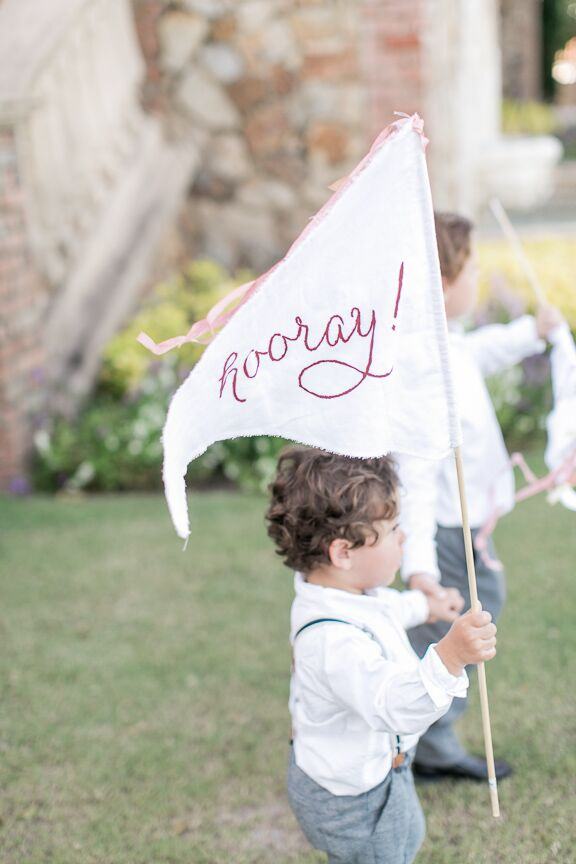 "Michelle and Michael's son, Oliver, had just started to walk when he served as the couple's ring bearer. Complete with a white shirt and Zara suspenders, he was escorted down the aisle by two of his aunts. The couple's nephews walked ahead holding  ""Yay"" and ""Hooray"" stitched flags."