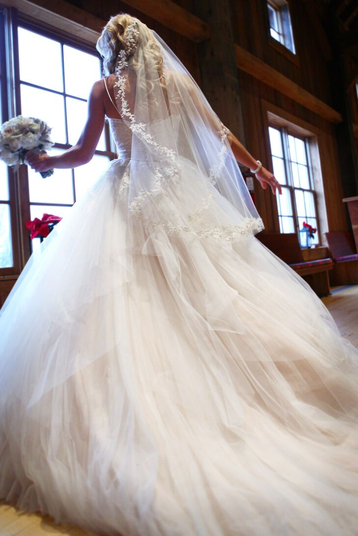 Lisa wore a strapless ivory wedding dress with a sweetheart neckline and a bodice accented in lace. The ball gown wedding dress had a full tulle skirt that flowed out. She wore an ivory tulle veil lined with lace that matched the rest of her elegant look.