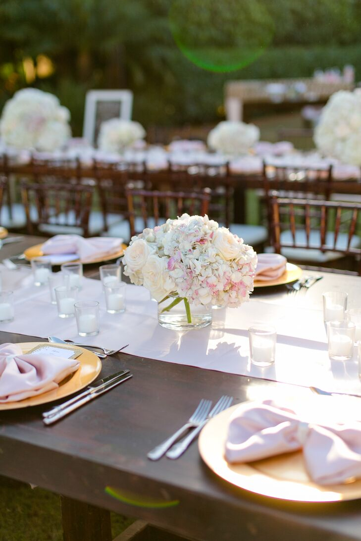 Lauren and Andy really wanted their tablescapes to make an impact against the lush hedges. So they worked with Signature Florals to design just that. Overflowing arrangements of white and pink hydrangeas as well as blush garden roses lined every blush silk runner along the cherrywood tables.