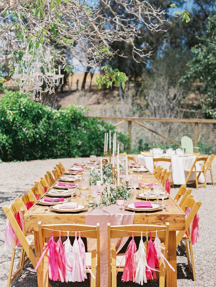Guests sat at wooden dining tables draped with sparkly pink runners. Each chair had pink and neutral-colored tassels hanging on the back, and tall white candles mixed with garlands served as centerpieces.