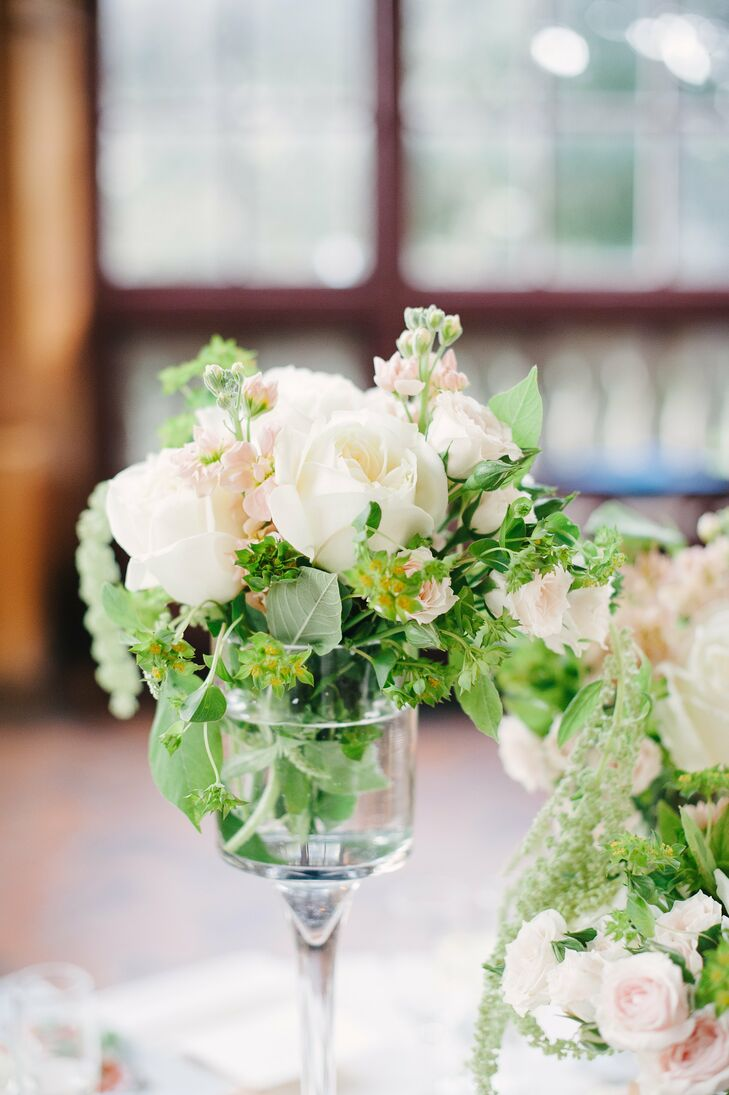 In addition to the tall centerpieces, some tables had miniature centerpieces that were filled with blush and ivory roses.