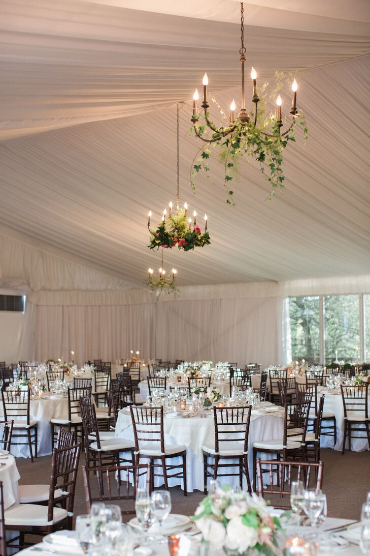 Dinner and dancing unfolded under a spacious tent overlooking the golf course, with panels of ethereal fabric giving the space a sense of whimsy and romance. Weaving in the evening's garden theme, Rye Workshop draped the classic chandeliers with ivy and bright pink blooms.