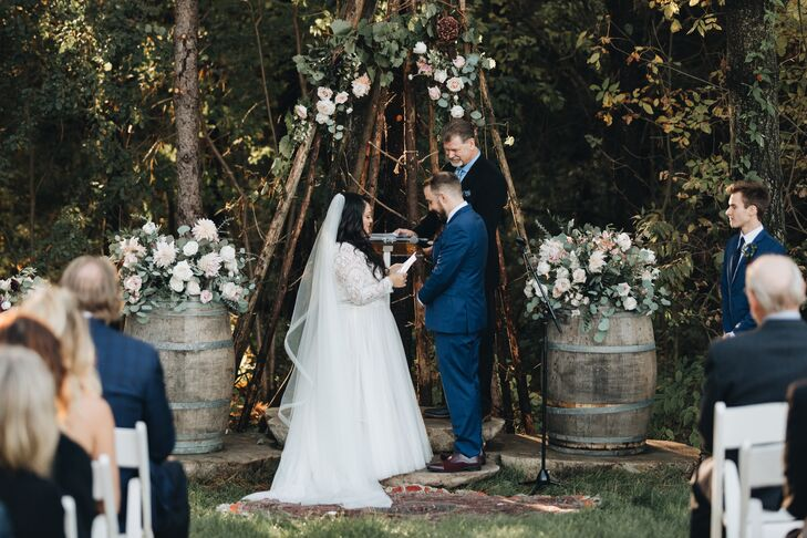 Couple Reciting Vows under Triangle Branch Arch