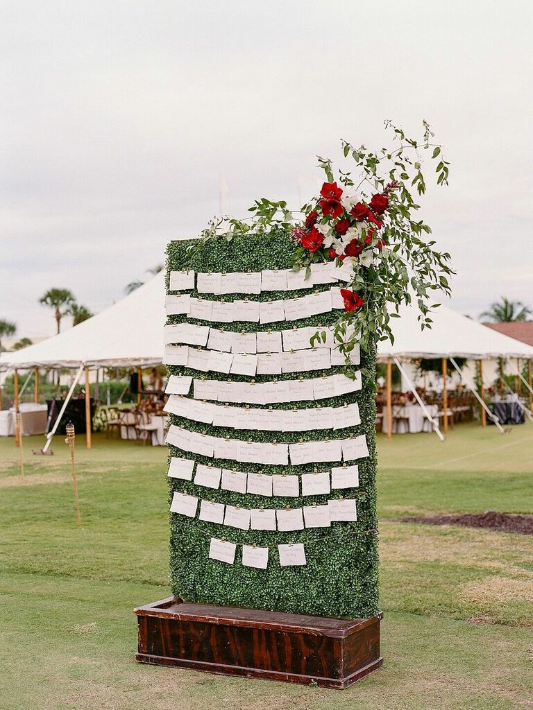 Escort card display on greenery wall with red floral arrangement as decoration