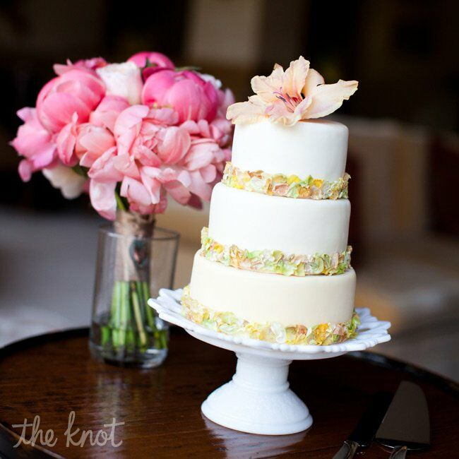 The simple, three-tiered fondant cake was dressed up with multicolored fabric flowers around the base of each tier.