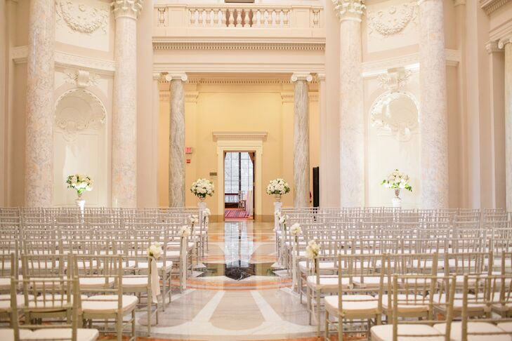 The ceremony was held in the rotunda at the Carnegie Institute of Washington. The hall has tall marble pillars and a clean, white color scheme, making it a versatile space. Floral arrangements of white hydrangeas on stands at the altar echoed the hall's tall pillars.