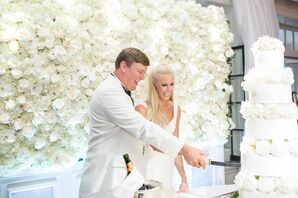 Cake Cutting Against White Flower Wall