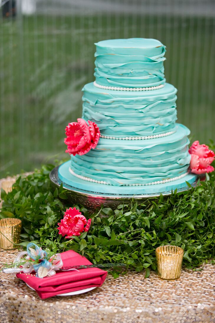 The three-tier cake matched the wedding colors with teal ruffled fondant and pink sugar flowers. Inside the cake was red velvet with buttercream, banana  nut with caramel and vanilla with raspberry and vanilla cream.