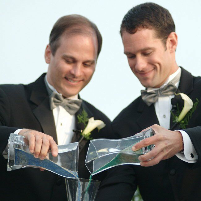 Doug and Dan were married just before sunset at the highest point in Provincetown at the base of the Provincetown Monument. Guests were seated facing the harbor, with a stunning view of Cape Cod in the background. The couple recited vows and incorporated both a unity sand ceremony, to celebrate the joining of their families, and the Jewish tradition of breaking a glass, to symbolize the permanency of marriage.